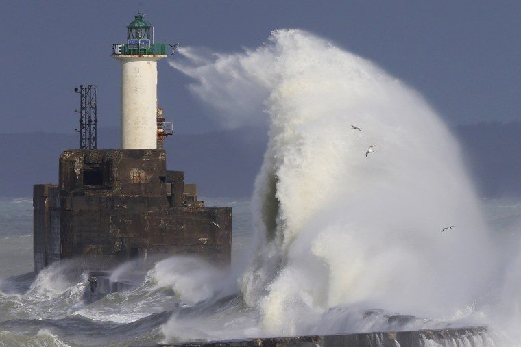 Image: Waves crash against a lighthouse as the wind blows at around 62 mph