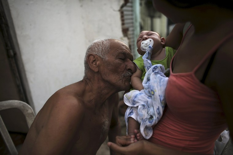 Image: Great-grandfather Wilson kisses his great-grandson Juan Pedro who is 2-months old and born with microcephaly as his mother Daniele Santos holds him on a street in Recife