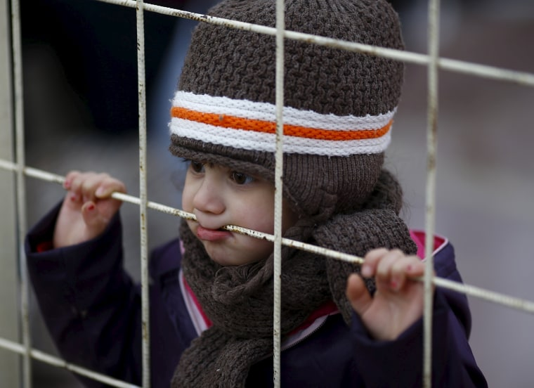 Image: A Syrian boy looks through a gate as others wait to cross into Syria at Oncupinar border crossing in the southeastern city of Kilis