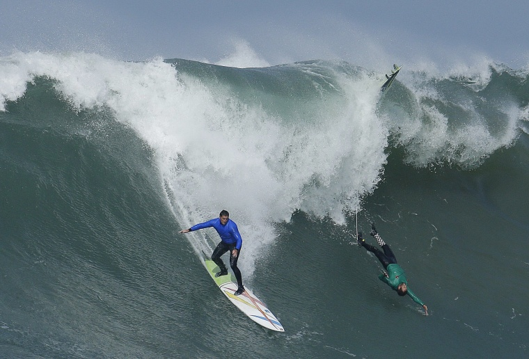 Image: Ben Wilkinson, left, surfs beside Greg Long who wipes out on a giant wave