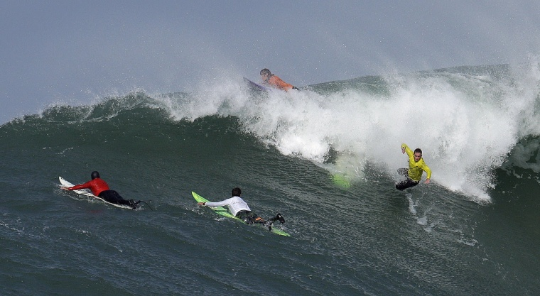 Image: Zach Wormhoudt, right, wipes out on a giant wave during the third heat of the Mavericks surfing contest