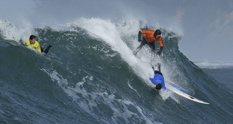 Image: Grant Washburn rides a wave as Dave Wassel wipes out