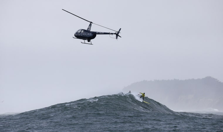 Image: Carlos Burle, of Brazil, surfs a giant wave during the finals of the Mavericks surfing contest