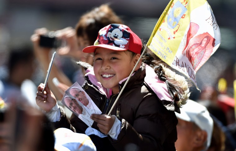 Image: A young girl waits for the passage of Pope Francis on his way to the Nuncianture, in Mexico City