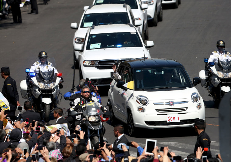 Image: Pope Francis waves to the crowd while leaving Zocalo Square in Mexico City