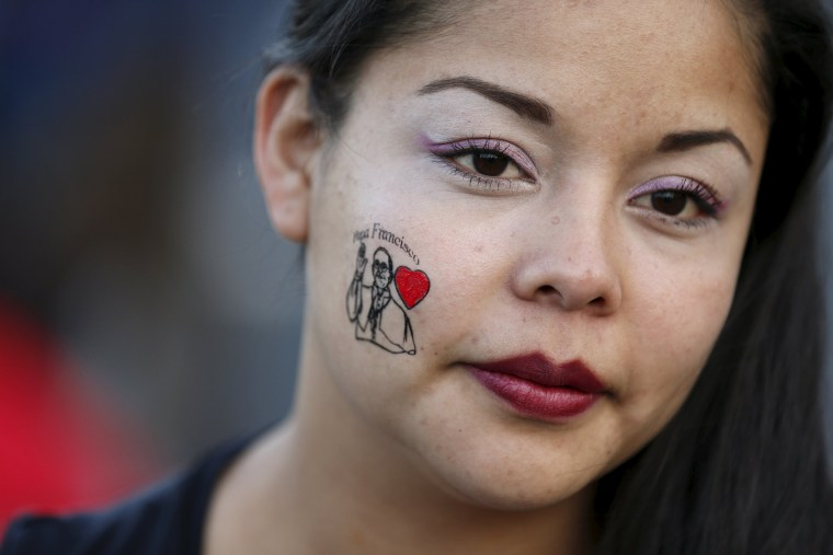 Image: A woman sports a face painting depicting Pope Francis in Mexico City