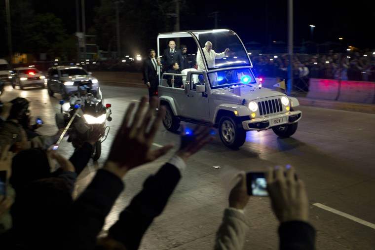 Image: Pope Francis waves to people from the popemobile on his route to the Apostolic Nunciature