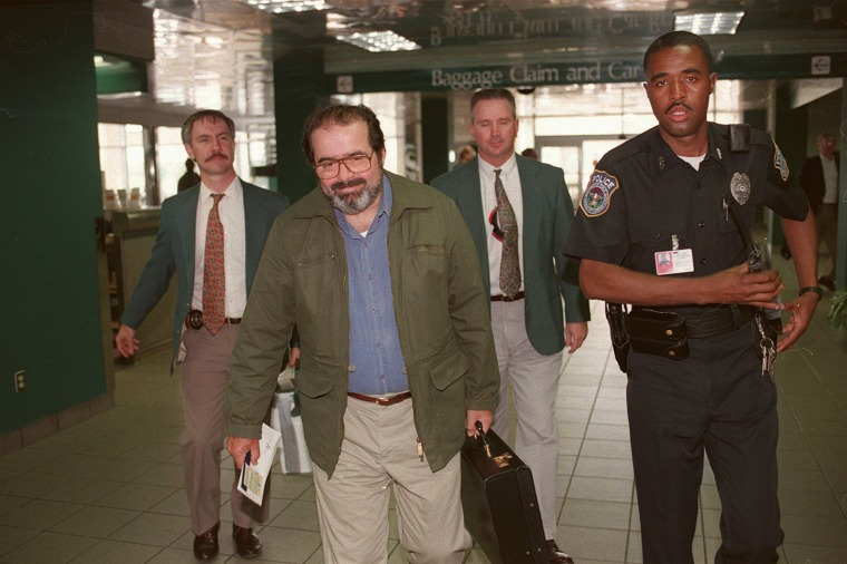 Image: Scalia has the smile of a successful hunter as he is escorted through the Jackson International Airport