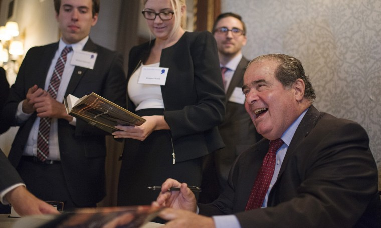 Image: Scalia smiles while signing his book