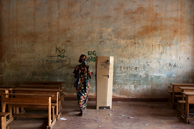 Image: A woman walks to a polling booth during the second round of presidential and legislative elections in the mostly muslim PK5 neighbourhood of Bangui, Central African Republic