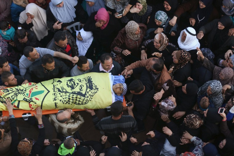 Image: Mourners carry the body of Palestinian teenager Nihad Waked, 15, who was shot dead by Israeli troops on Sunday, during his funeral near the West Bank city of Jenin