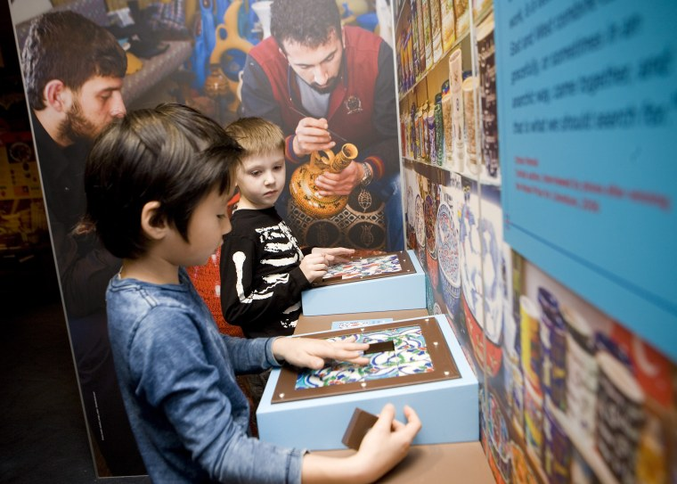"Children feel ceramic tiles at a stall in the global marketplace at the Children's Museum of Manhattan's new exhibit, ""America to Zanzibar: Muslim Cultures Near and Far."""
