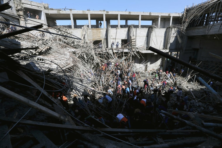 Image: People gather as members of the Palestinian Civil Defence search for casualties