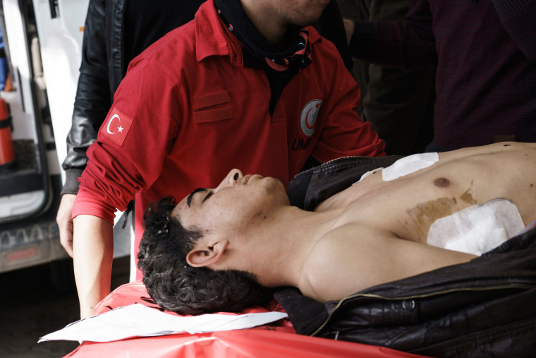 Image: Turkish medics carry a wounded Syrian to a hospital in Kilis, Turkey after bombing in Northern Syria