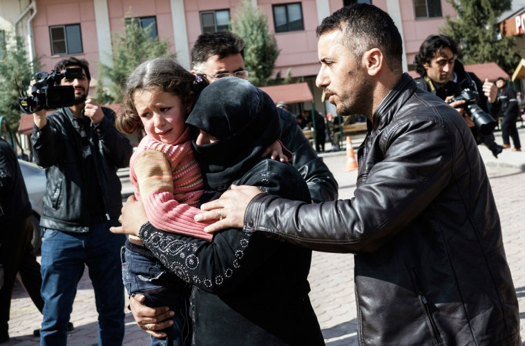 Image: A Turkish man helps a Syrian woman carrying a wounded Syrian girl to a hospital in Kilis, Turkey after airstrikes in Northern Syria
