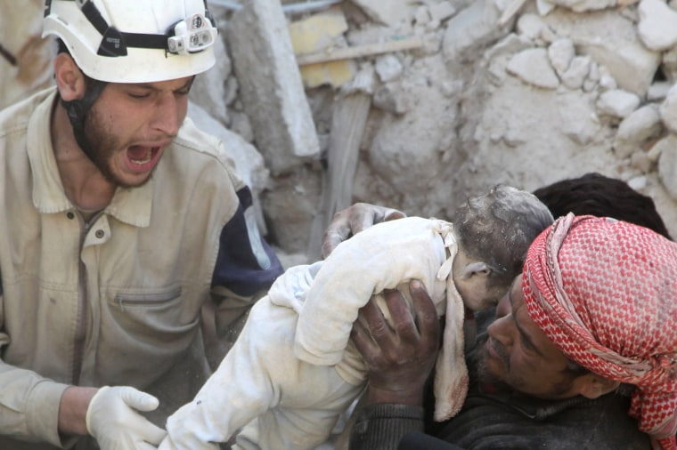 Image: A man holds the body of a dead child as a civil defence member reacts after airstrikes by pro-Syrian government forces in the rebel held al-Qaterji neighbourhood of Aleppo,