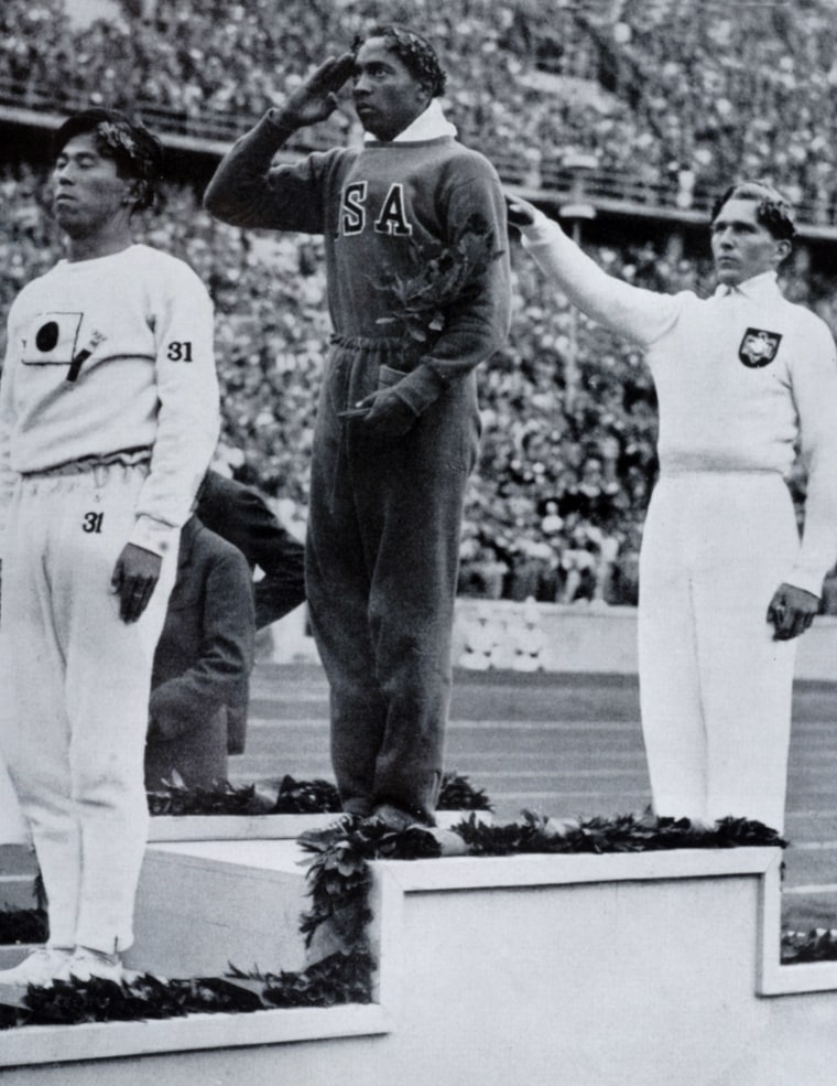 Sport, 1936 Olympic Games in Berlin, Mens Long Jump, Medal Ceremony, USA's Jesse Owens, centre, salutes the flag after winning the Gold medal, with left, Naoto Tajima, Japan (bronze medal), right, Luz Long, Germany, (silver medal) (Photo by Popperfoto/Getty Images)