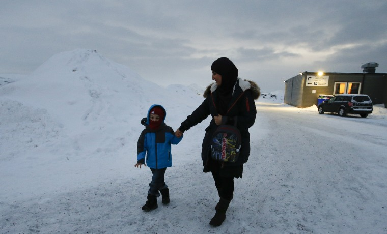 Image: Refugee Huda al-Haggar and her son Omar walk outside the refugee camp in Hammerfest
