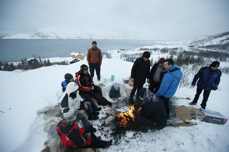 Image: Asylum seekers gather round a fire as they cook a meal overlooking the temporary Altnes camp refugee camp