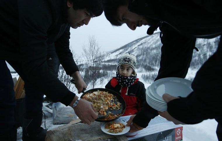 Image: Afghan asylum seeker Roheek Yausofi waits his turn for food cooked on an open fire
