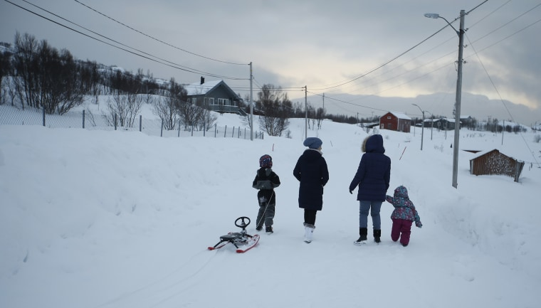 Image: Asylum seekers take their children fro a walk near the temporary accommodation at the Altnes camp