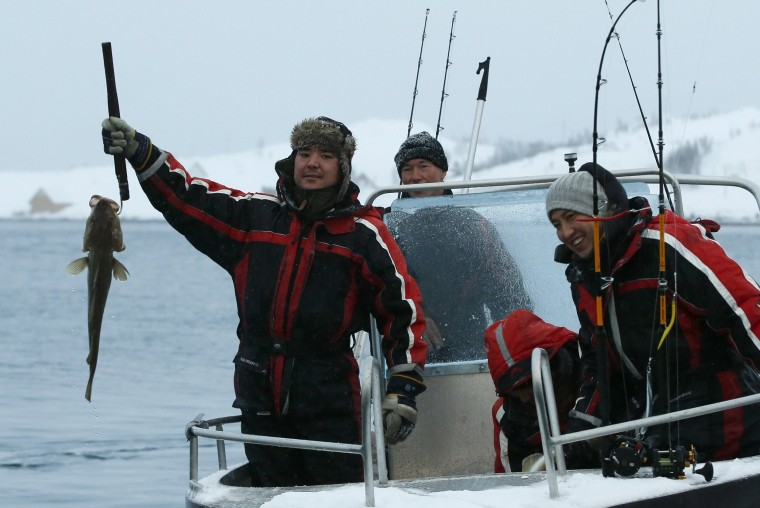 Image: Stig Erland Hansen, center, owner of the Altnes camp, returns from a fishing trip with asylum seekers