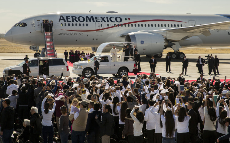 Image: People wave and take pictures of Pope Francis in his popemobile as he arrives to Benito Juarez International Airport