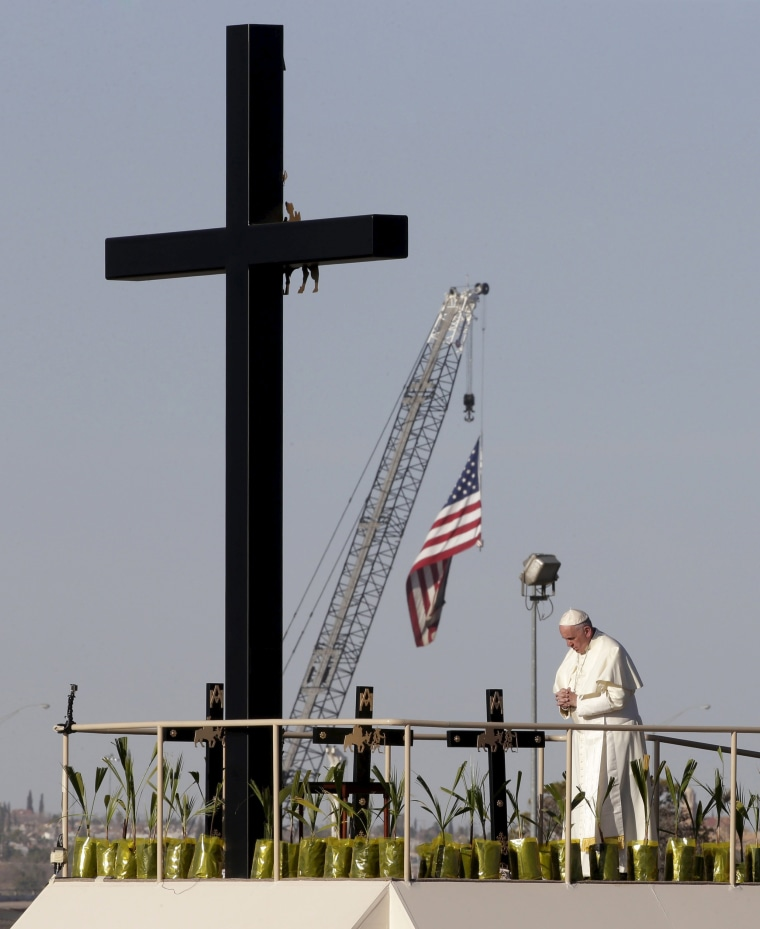 Image: Pope Francis stands next to a wooden cross at the border between Mexico and the U.S. in Ciudad Juarez,