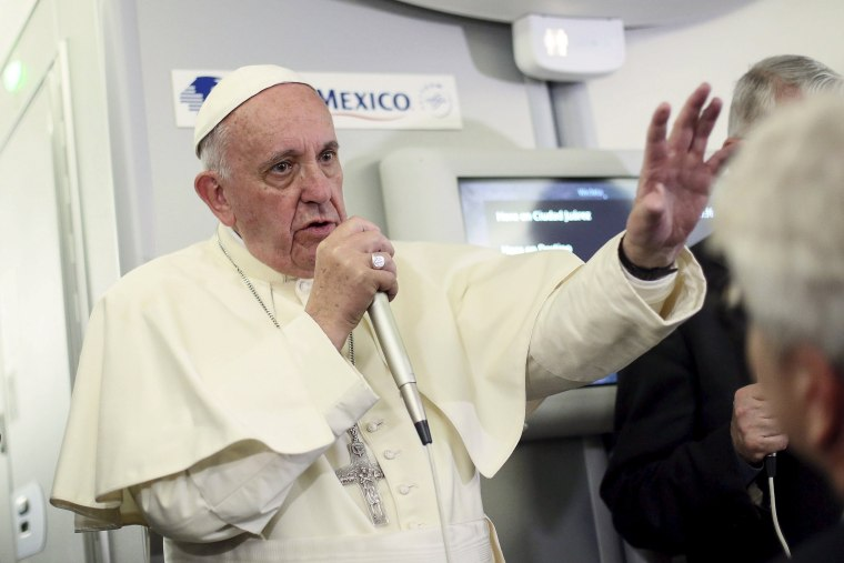 Image: Pope Francis gestures during a meeting with the media onboard the papal plane while en route to Rome