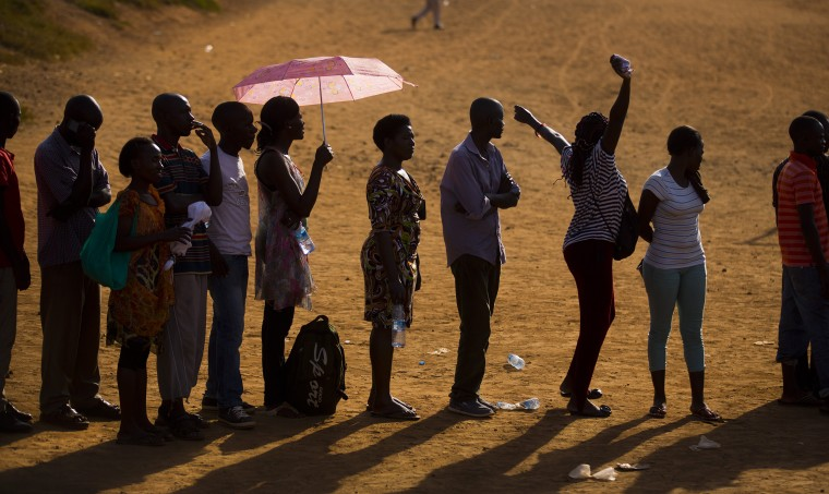 Image: A voter stretches her arms as she and other Ugandans continue to queue to cast their votes at sunset in the capital Kampala