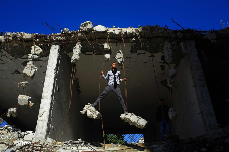 Image: Palestinians play in the ruins of a building in Gaza City