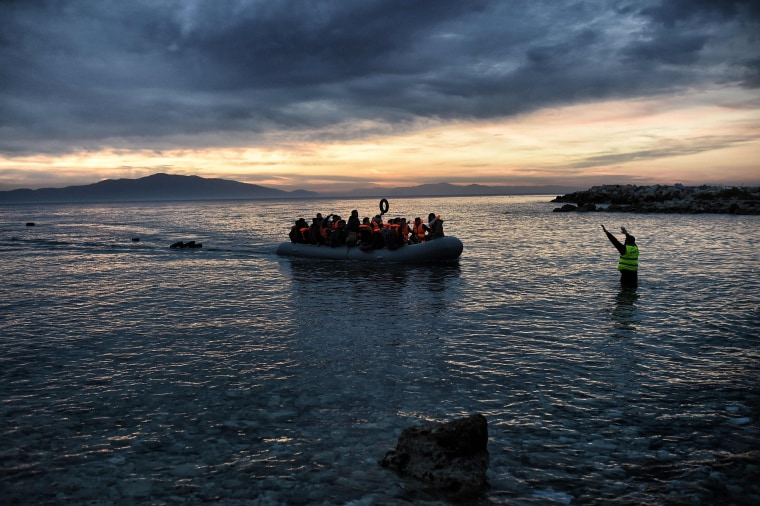 Image: Refugees and migrants massed onto an inflatable boat reach Mytilene