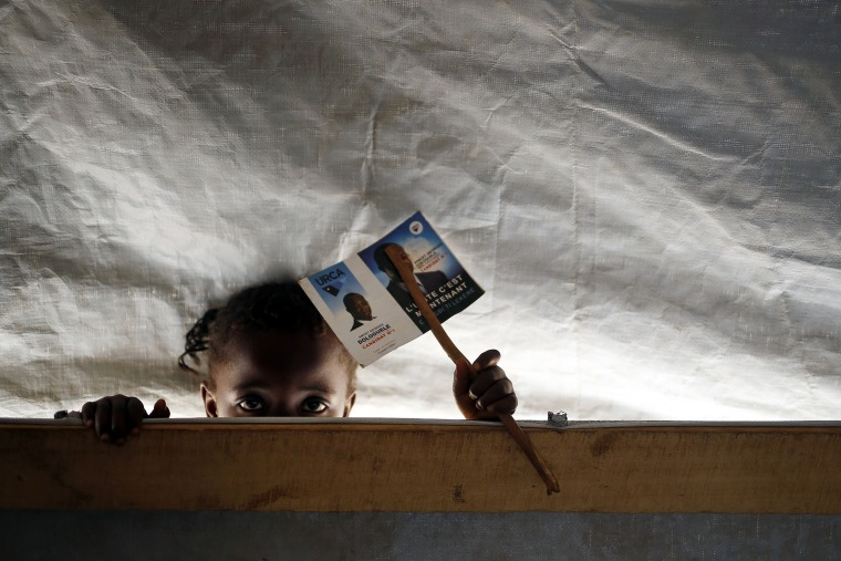 Image: A child peeks through a classroom in a school set in the Mpoko refugee camp