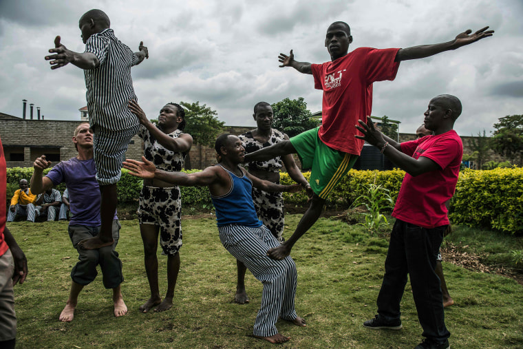 Image: Prisoners try some acrobatic figures during a workshop with the Sarakasi circus performers