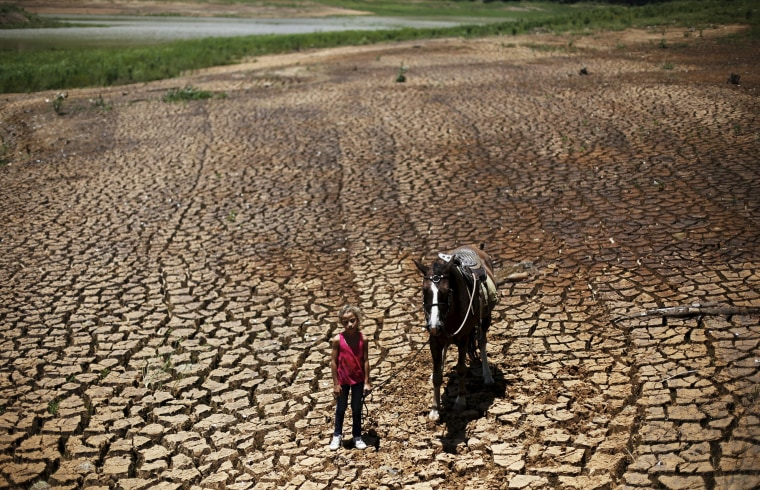 Image: Paula poses with her horse on the cracked ground of Atibainha dam