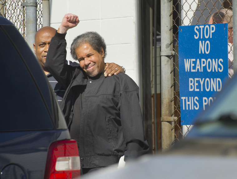 Image: Albert Woodfox, right, raises a clenched fist as he walks out of the West Feliciana Detention Center