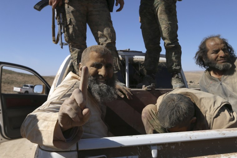 Image: An Islamic State fighter gestures while being held as prisoner