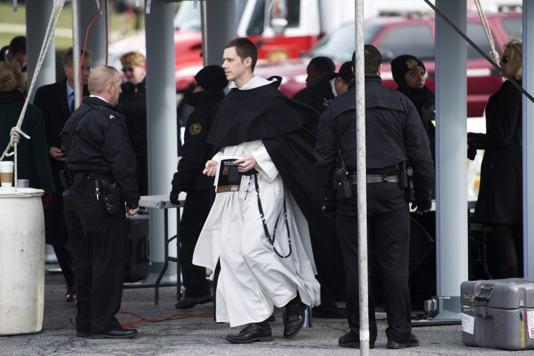 Image: A clergy member walks out of security screening prior to the funeral services