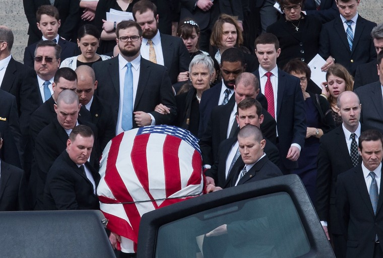 Image: Scalia's family follows his casket after the funeral