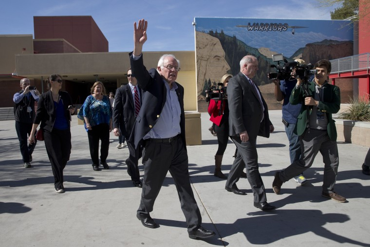 Image: Sanders waves to voters as he leaves a caucus site