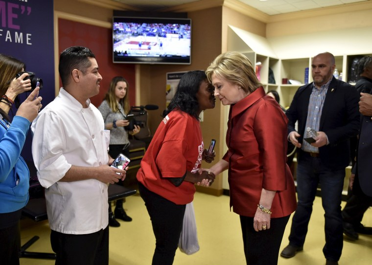 Image: Clinton meets employees during a campaign stop on caucus day
