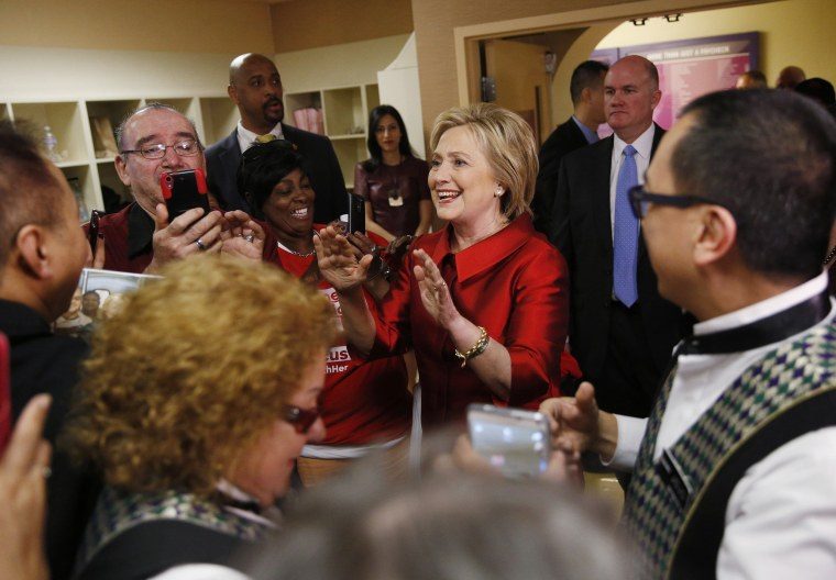 Image: Clinton reacts as employees of Harrah's Las Vegas surround her during a visit