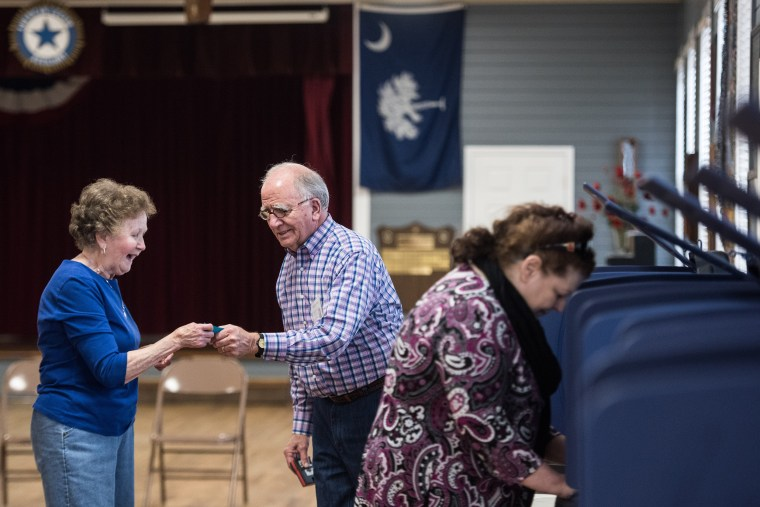 Image: A poll worker assists a Republican primary voter at American Legion Post 7