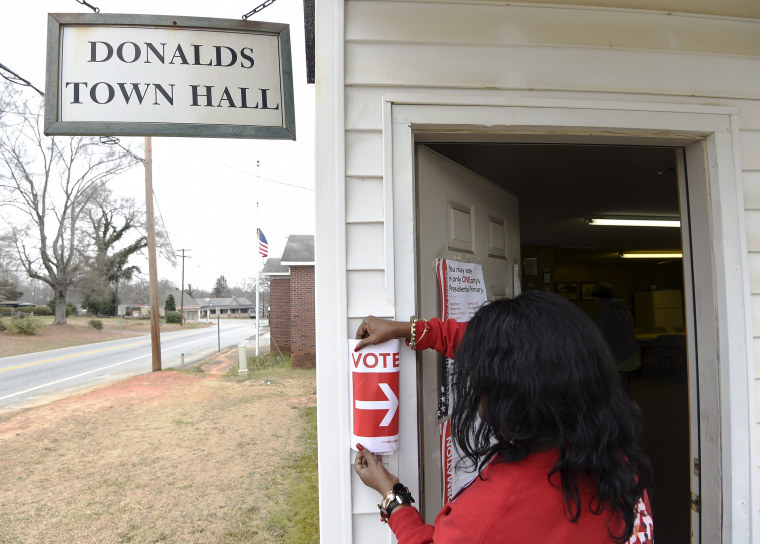 Image: Election worker Beverly Smith places a sign on the Donalds Town Hall polling place in preparations for voting in the U.S. Republican presidential primary in Donalds, South Carolina