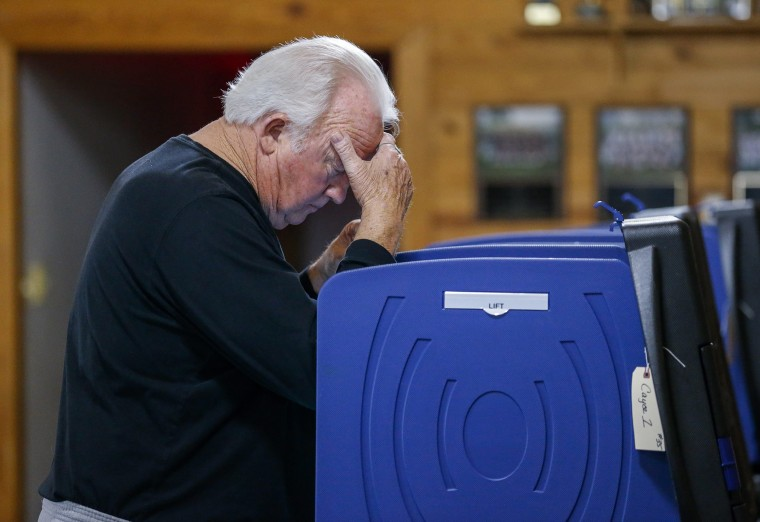 Image: Basil Mack decides who to vote for at an American Legion Hall in Cayce