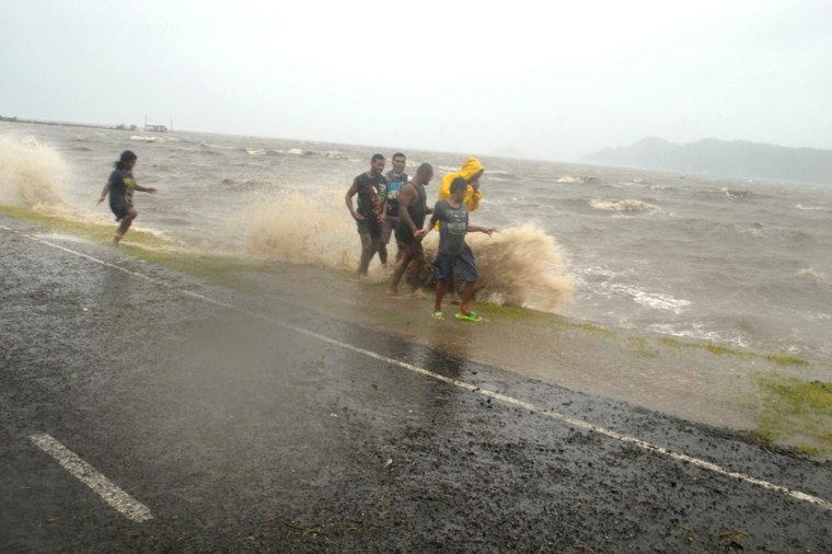 Image: People are splashed by a wave whipped up by the encroaching cyclone