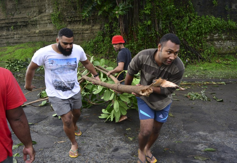Image: Fijian men clear a road of a fallen tree in Fiji's capital Suva after Cyclone Winston swept across Viti Levu Island