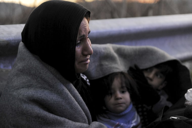 Image: An Afghan mother cries as she covers herself and her children with a blanket while trying to reach the Greek-Macedonian border, following reports that Macedonia has closed its borders with Greece to Afghan migrants