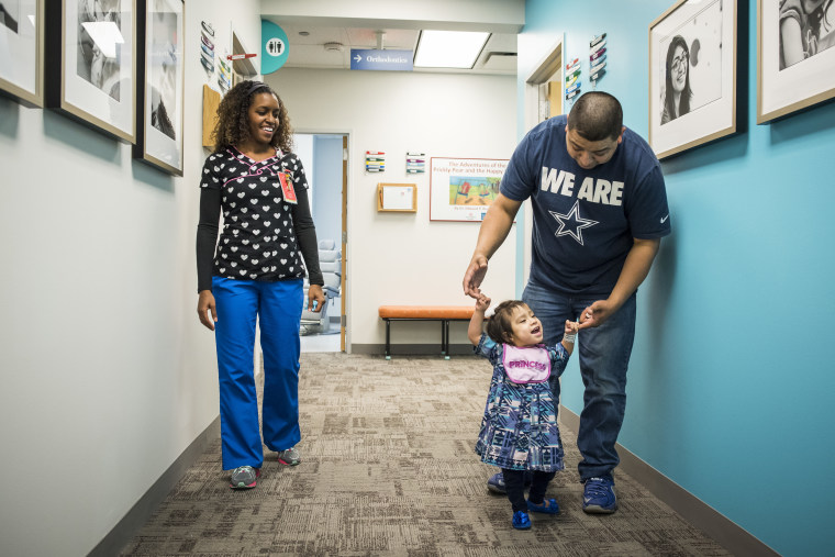 Eric Mata holds daughter Knatalye's hands as she walks down the hall of a clinic at Texas Children's Hospital.