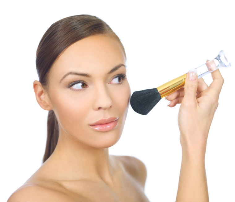 woman applying makeup with brush
